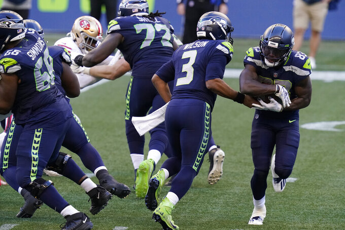 Seattle Seahawks quarterback Russell Wilson (3) hands off to wide receiver David Moore (83) during the second half of an NFL football game against the San Francisco 49ers, Sunday, Nov. 1, 2020, in Seattle. (AP Photo/Elaine Thompson)