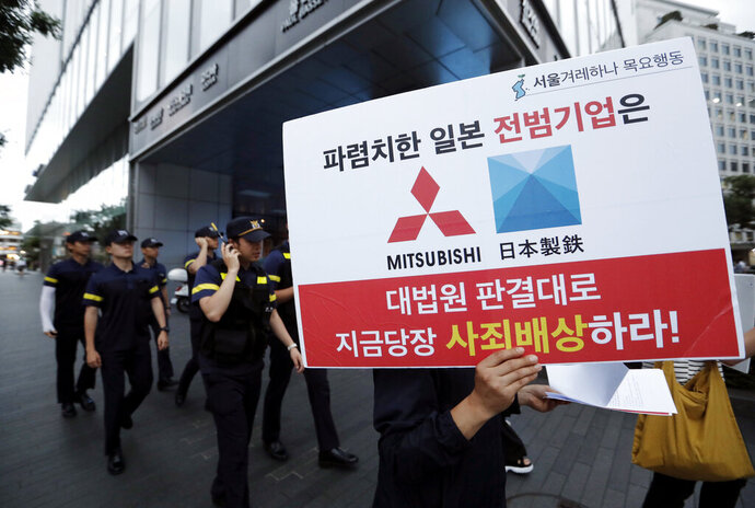 FILE - In this July 11, 2019, file photo, a protester with a banner walks to attend a rally denouncing the Japanese government's decision on their exports to South Korea in front of the Japanese Embassy in Seoul, South Korea. The modern legacy of a dark chapter in Japan's history, when hundreds of thousands of people were brought from the Korean Peninsula and other Asian nations to work in logging, in mines, on farms and in factories as forced labor, lives on in the companies that came to dominate the Japanese economy after World War II. Many of those companies are still facing demands for compensation that they say were settled by treaty decades ago. The sign reads