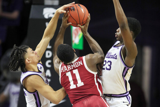 Oklahoma guard De'Vion Harmon (11) has a shot blocked by Kansas State guard Mike McGuirl, left, with help from forward Montavious Murphy (23) during the second half of an NCAA college basketball game in Manhattan, Kan., Wednesday, Jan. 29, 2020. Kansas State won 61-53. (AP Photo/Orlin Wagner)