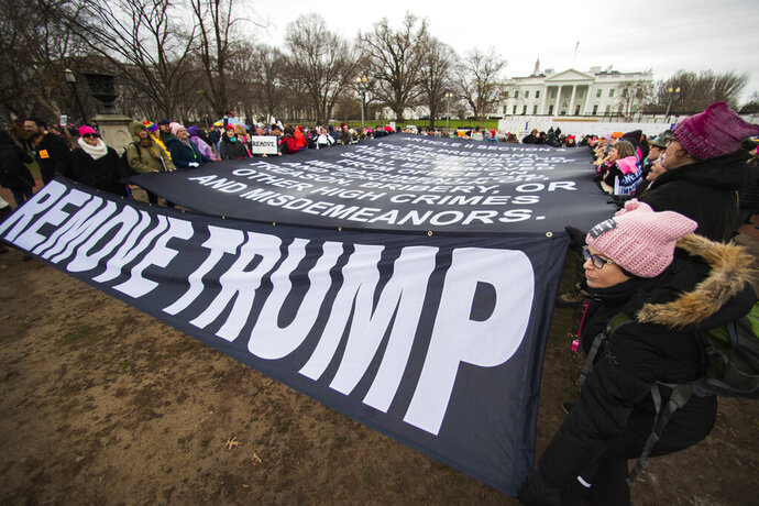 Participants of the Women's March hold banners near the White House, Saturday, Jan. 18, 2020, in Washington, three years after the first march in 2017, the day after President Donald Trump was sworn into office. (AP Photo/Manuel Balce Ceneta)