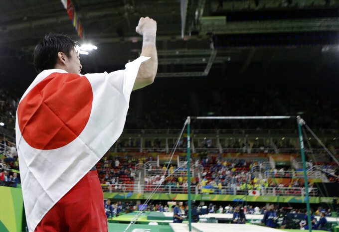 FILE - In this Aug. 10, 2016, file photo, Japan's Kohei Uchimura celebrates his gold during the artistic gymnastics men's individual all-around final at the 2016 Summer Olympics in Rio de Janeiro, Brazil. Tokyo Olympic organizers are expected to unveil their fifth annual budget before Christmas. It is expected to show the rising costs of the postponed Games. (AP Photo/Rebecca Blackwell)