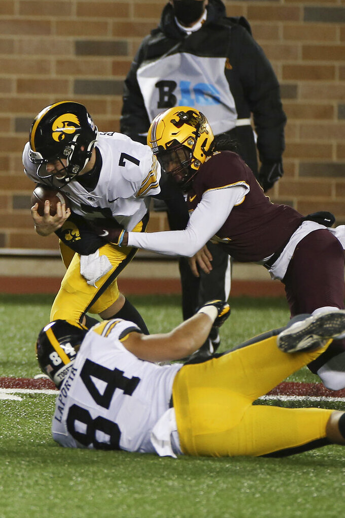 Minnesota defensive back Michael Dixon, top right, tackles Iowa quarterback Spencer Petras (7) during the second half of an NCAA college football game Friday, Nov. 13, 2020, in Minneapolis. Iowa won 35-7. (AP Photo/Stacy Bengs)