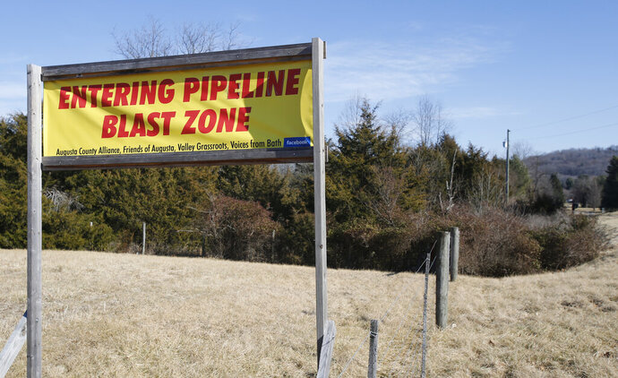 FILE - This Feb. 8, 2018, file photo shows a sign along a highway to protests the route of the Atlantic Coast Pipeline in Deerfield, Va. The developers of the Atlantic Coast Pipeline announced Sunday, July 5, 2020, that they are canceling the multi-state natural gas project, citing delays and increasing cost uncertainty. (AP Photo/Steve Helber, File)