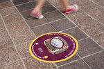 FILE - In this Feb. 5, 2021, file photo, a child walks past a marker for a past Super Bowl Champion as she walks along the Hillsborough River in Tampa, Fla. The city is hosting Sunday's Super Bowl 55 football game between the Tampa Bay Buccaneers and the Kansas City Chiefs. (AP Photo/Charlie Riedel, File)