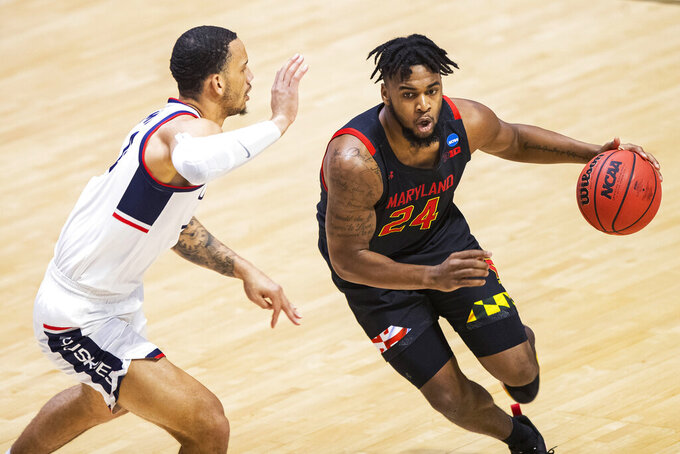 Maryland's Donta Scott (24) drives against Connecticut's Tyrese Martin during the first half of a first-round game in the NCAA men's college basketball tournament Saturday, March 20, 2021, at Mackey Arena in West Lafayette, Ind. (AP Photo/Robert Franklin)