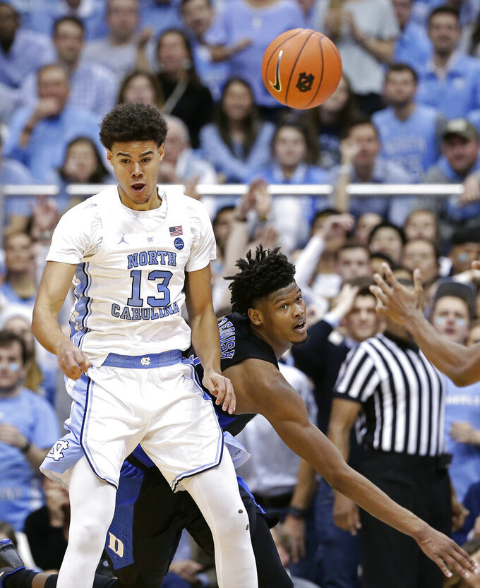 North Carolina's Cameron Johnson (13) and Duke's Cam Reddish struggle for the ball during the second half of an NCAA college basketball game in Chapel Hill, N.C., Saturday, March 9, 2019. North Carolina won 79-70. (AP Photo/Gerry Broome)