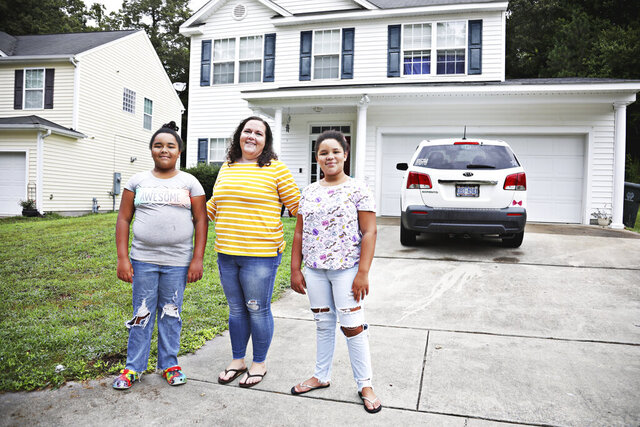 Kortni Carter, center, stands with her daughters Keira, 11, left and Karmyn, 10, right, in Raleigh, N.C.  Carter is preparing her daughters  for online school at their home for at least the first two weeks of the school year, if not longer. (Juli Leonard/The News & Observer via AP)