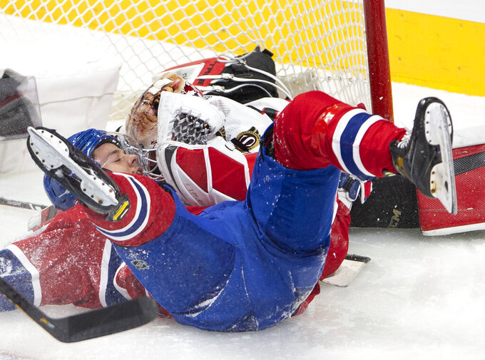 Montreal Canadiens center Jesperi Kotkaniemi (15) crashes against Ottawa Senators goaltender Joey Daccord (34) during the second period of an NHL hockey game Tuesday, March 2, 2021, in Montreal. (Ryan Remiorz/The Canadian Press via AP)