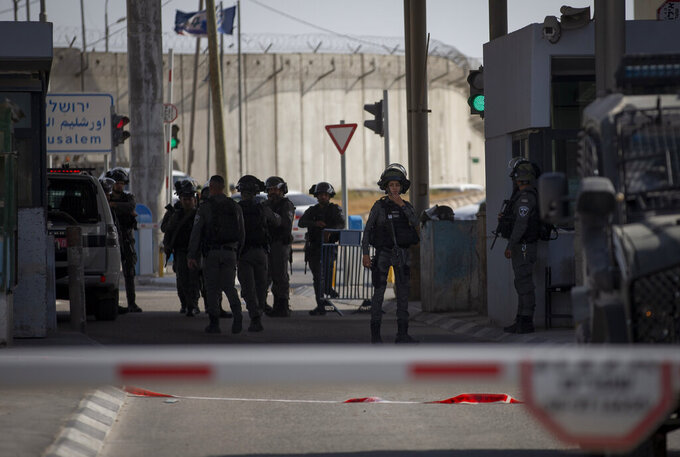 Members of the Israeli forces gather at the site where a woman was shot and killed at the Qalandia checkpoint between Jerusalem and the West Bank city of Ramallah, Saturday, June 12,  2021.  Israeli police say a private security guard at the checkpoint shot and killed the woman who allegedly planned to carry out a stabbing attack. The police said in a statement that the guard saw the woman with a knife and shot her.(AP Photo/Majdi Mohammed)
