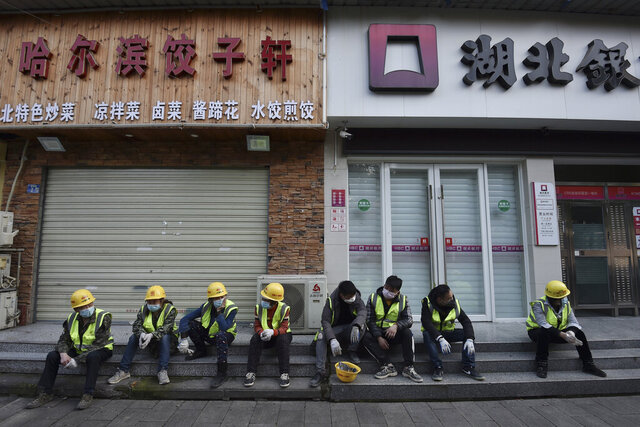 In this Sunday, Feb. 23, 2020, photo, workers take a rest near the closed restaurant and bank in Wuhan in central China's Hubei province. Warning that China's virus epidemic is
