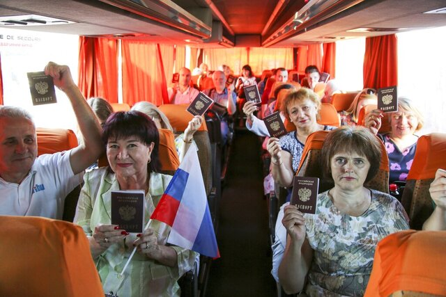 In this photo taken on Saturday, June 27, 2020, people show their Russian passports sitting on a bus to Russia at a bus to Russia at a bus stop in Donetsk, eastern Ukraine. Residents of separatist-controlled regions in eastern Ukraine who have Russian citizenship are traveling to Russia to vote on constitutional amendments that would allow President Vladimir Putin to remain in power until 2036. Authorities of the self-proclaimed Luhansk and Donetsk People's Republics have organized bus services to polling stations in the neighboring Rostov region in Russia, in what is seen by many as part of the wide-spread effort to boost turnout at the controversial plebiscite. (AP Photo/Alexei Alexandrov)