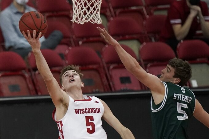 Wisconsin's Tyler Wahl shoots past Wisconsin-Green Bay's Lucas Stieber during the first half of an NCAA college basketball game Tuesday, Dec. 1, 2020, in Madison, Wis. (AP Photo/Morry Gash)