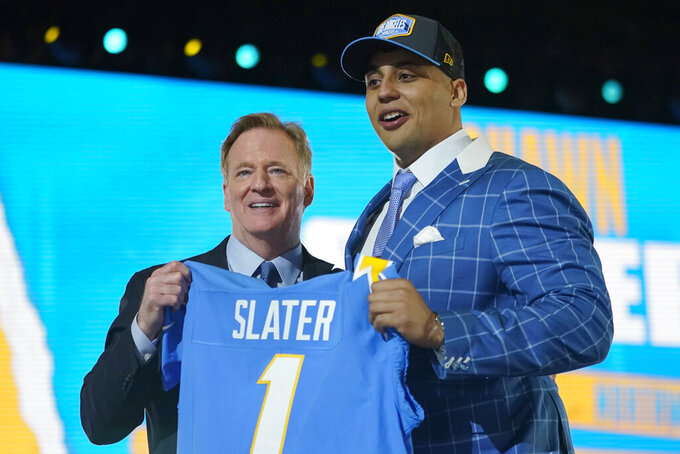 Northwestern tackle Rashawn Slater, right, holds a team jersey with NFL Commissioner Roger Goodell after the Los Angeles Chargers selected him with the 13th pick in the NFL football draft Thursday April 29, 2021, in Cleveland. (AP Photo/Tony Dejak)