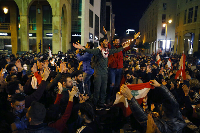 Protesters chant slogans during ongoing protests against the Lebanese political class, as riot police block a road leading to the parliament building in Beirut, Lebanon, Sunday, Dec. 8, 2019. A possible candidate for prime minister of Lebanon said Sunday he is withdrawing from consideration for the post, prolonging the country's political crisis. (AP Photo/Bilal Hussein)