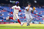 Philadelphia Phillies' Odubel Herrera, left, and Colorado Rockies' Carlos Estevez react as Herrera grounds out to end a baseball game, Sunday, Sept. 12, 2021, in Philadelphia. (AP Photo/Matt Slocum)