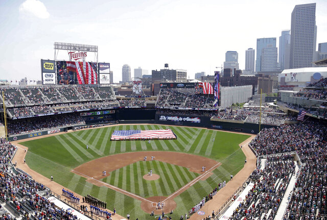 FILE - In this June 30, 2013 file photo, members of the Armed Forces hold a large flag at Target field in Minneapolis where the Minnesota Twins hosted Armed Forces Appreciation Day prior to the baseball game between the Twins and the Kansas City Royals. The 2021 NHL Winter Classic will be hosted by the Minnesota Wild at Target Field, the home stadium of the MLB's Twins. NHL officials announced the site for next Winter Classic during this season's game Wednesday, Jan. 1, 2020 at Cotton Bowl Stadium in Dallas. (AP Photo/Jim Mone, File)