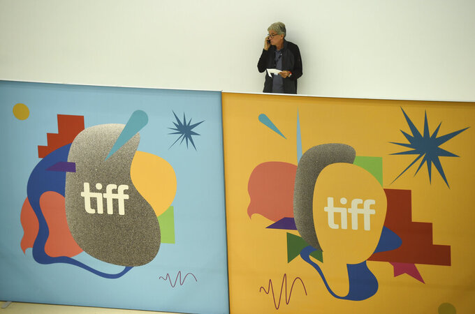 FILE - An attendee appears above signage at the Toronto International Film Festival on Sept. 5, 2019, in Toronto. Festival organizers  announced that the 45th edition of TIFF will take place Sept. 9-18 and return to in-person screenings in many of its usual downtown Toronto venues, like the TIFF Bell Lightbox, Roy Thomson Hall, and the Princess of Wales Theatre. (Photo by Chris Pizzello/Invision/AP, File)