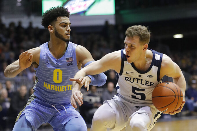 Butler's Paul Jorgensen (5) is defended by Marquette's Markus Howard (0) during the first half of an NCAA college basketball game, Wednesday, Jan. 30, 2019, in Indianapolis. (AP Photo/Darron Cummings)
