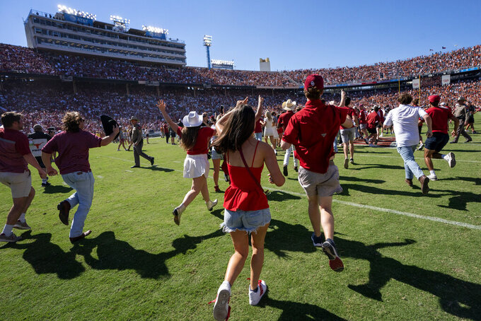 Oklahoma fans rush the field after their team beat Texas in an NCAA college football game at the Cotton Bowl, Saturday, Oct. 9, 2021, in Dallas. (AP Photo/Jeffrey McWhorter)