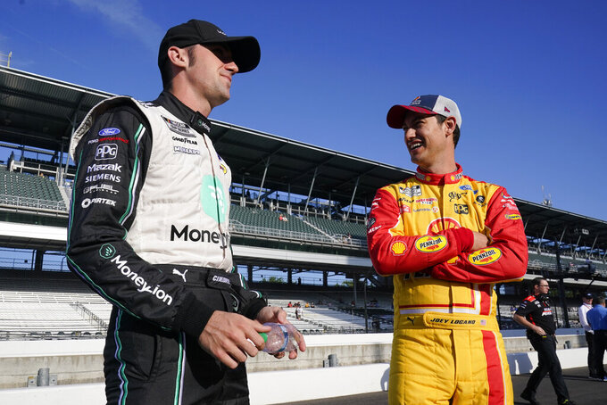 Austin Cindric, left, talks with Joey Logano before qualifications for the NASCAR Series auto race at Indianapolis Motor Speedway, Sunday, Aug. 15, 2021, in Indianapolis. (AP Photo/Darron Cummings)