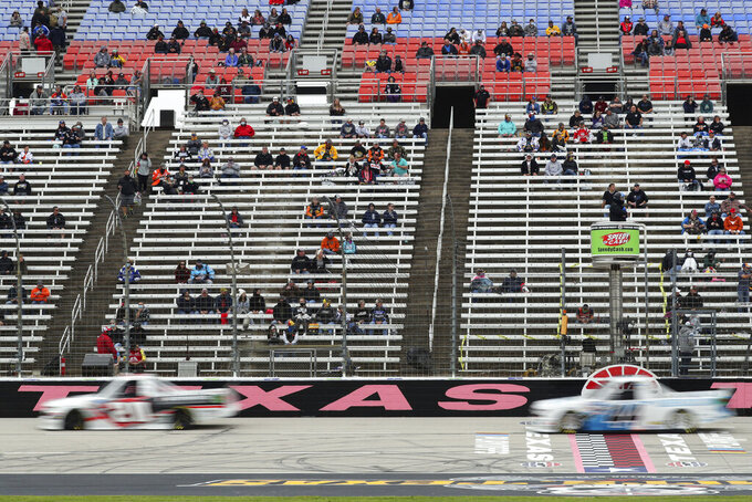 Fans watch a NASCAR Truck Series auto race at Texas Motor Speedway in Fort Worth, Texas, Sunday Oct. 25, 2020. (AP Photo/Richard W. Rodriguez)