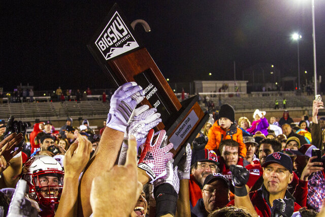 FILE - In this Nov. 21, 2015, file photo, Southern Utah celebrates with the trophy after defeating Northern Arizona in an NCAA college football game for the Big Sky Conference title Cedar City, Utah. The Big Sky Conference postponed its football season on Friday, Aug. 7, 2020, to the spring because of the coronavirus pandemic and called for the FCS playoffs to be moved to the second semester as well.(Jordan Allred/The Spectrum via AP)