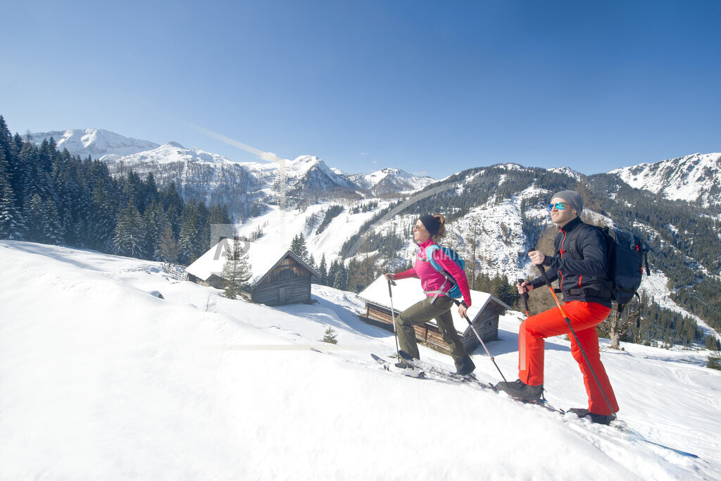 Young couple with skis hiking on snow