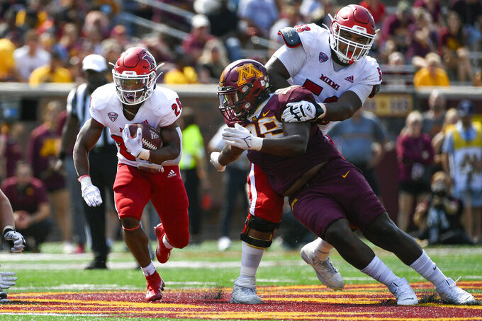 Miami-Ohio running back Keyon Mozee, left, runs past Minnesota defensive lineman Nate Becker while offensive line Caleb Shaffer tries to hold him back during the first half of an NCAA college football game on Saturday, Sept. 11, 2021, in Minneapolis. Minnesota won 31-26. (AP Photo/Craig Lassig)