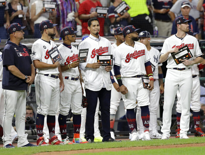 FILE - In this July 9, 2019, file photo, Cleveland Indians pitcher Carlos Carrasco, center without a hat, stands with Indians teammates during the fifth inning of the baseball All-Star Game in Cleveland, as part of Major League Baseball's