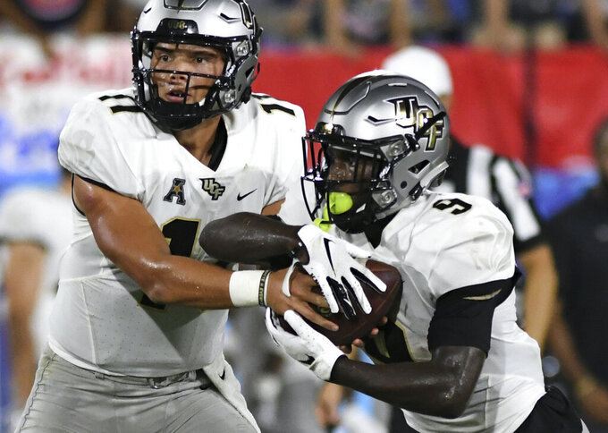 UCF quarterback Dillon Gabriel (11) hands the ball off to running back Adrian Killins Jr. (9) during the first half of an NCAA college football game against Florida Atlantic on Saturday, Sept. 7, 2019, in Boca Raton, Fla. (AP Photo/Jim Rassol)