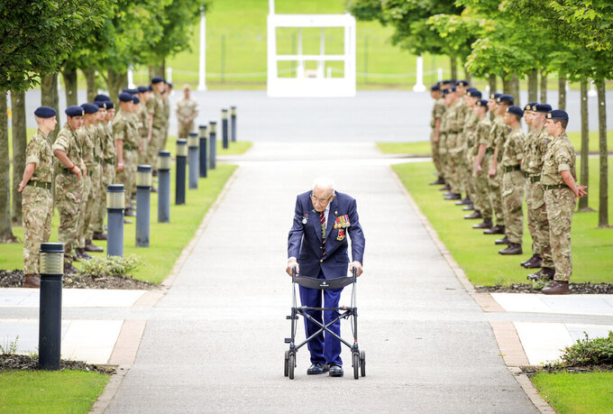 FILE - In this Aug. 3, 2020 file photo, Captain Sir Tom Moore walks down a guard of honour during a visit to the Army Foundation College in Harrogate, England, as part of his new role as Honorary Colonel of the Northern military training establishment. Tom Moore, the 100-year-old World War II veteran who captivated the British public in the early days of the coronavirus pandemic with his fundraising efforts, has died, Tuesday Feb. 2, 2021. (Danny Lawson/PA via AP, File)