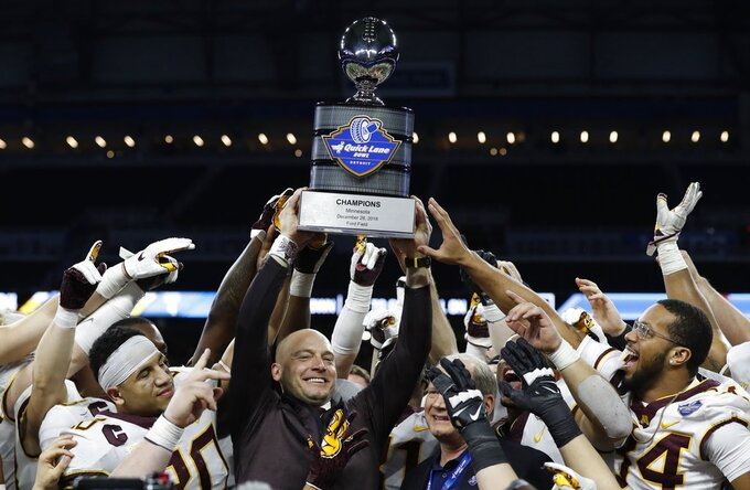 Minnesota head coach P.J. Fleck holds the champions trophy after the Quick Lane Bowl NCAA college football game against Georgia Tech, Wednesday, Dec. 26, 2018, in Detroit. Minnesota won 34-10. (AP Photo/Carlos Osorio)