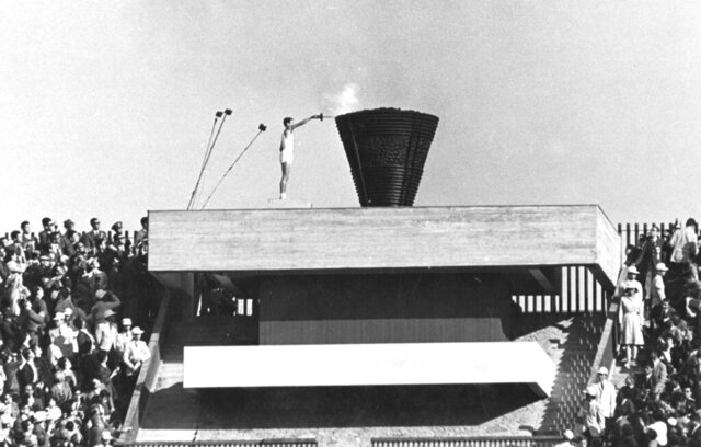 FILE - In this Oct. 10, 1964 file photo, Japanese runner Yoshinori Sakai lights the Olympic cauldron during the opening ceremony of the 1964 Summer Olympics in Tokyo. Sakai was born in Hiroshima on Aug. 6, 1945, the day the nuclear weapon destroyed that city. He symbolized the rebirth of Japan after the Second World War as he opened the 1964 Tokyo Games. Sakai was born in Hiroshima on Aug. 6, 1945, the day the United States dropped an atomic bomb on the city.  Just over 19 years later, he ran with the Olympic flame into the national stadium, left the cinder track, and jogged up a long flight of flower-lined stairs to reach the top.  (AP Photo/File)