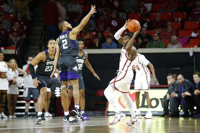 Oklahoma's De'Vion Harmon throws the ball away from TCU's Edric Dennis Jr. during the first half of an NCAA college basketball game in Norman, Okla., Saturday, Jan. 18, 2020. (AP Photo/Garett Fisbeck)