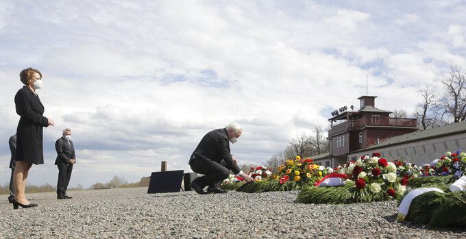 German President Frank-Walter Steinmeier, center, lays down a wreath during commemorations marking the 76th anniversary of the liberation of the Nazi concentration camp Buchenwald near Weimar, Germany, Sunday, April 11, 2021. On April 11, 1945 the US Army liberated the concentration camp Buchenwald. At left is Steinmeier's wife Elke Buendenbender. (AP Photo/Markus Schreiber)