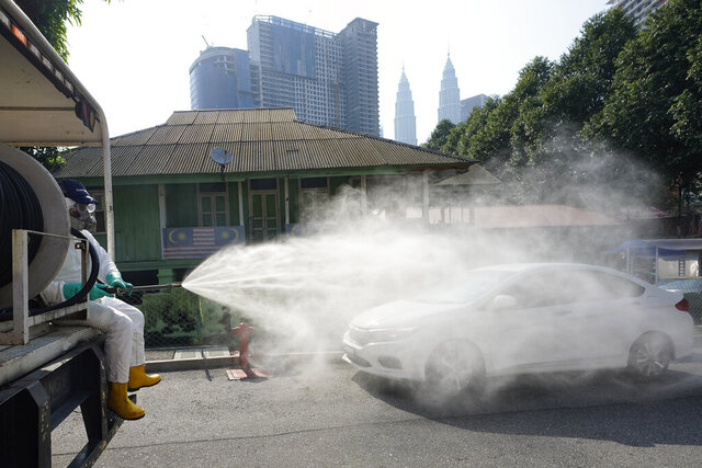 Health officials spray disinfectant in a Kampung Baru, traditional Malay village, in Kuala Lumpur city center as a safety precaution against the new coronavirus, Tuesday, March 31, 2020. The Malaysian government issued a restricted movement order to the public for the rest of the month to help curb the spread of the coronavirus. (AP Photo/Vincent Thian)