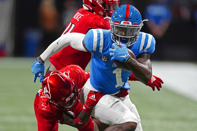 Mississippi wide receiver Jonathan Mingo (1) tries to escape from Louisville defensive back Kei'Trel Clark (13) during the second half of an NCAA college football game Monday, Sept. 6, 2021, in Atlanta. (AP Photo/John Bazemore)