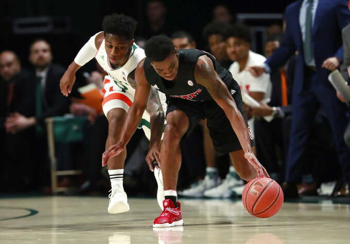 Miami guard Chris Lykes, left, and North Carolina State guard Markell Johnson battle for a loose ball during the first half of an NCAA college basketball game, Thursday, Jan. 3, 2019, in Coral Gables, Fla. (AP Photo/Wilfredo Lee)