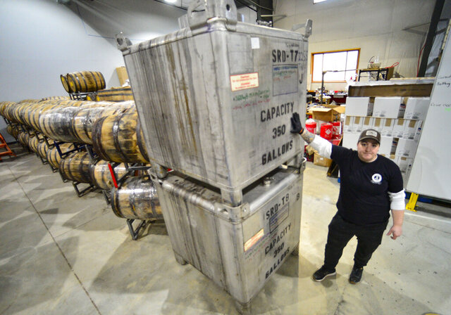 Alicia Porter, a worker at Saxtons River Distillery in Brattleboro, Vt., stands next to containers that are used to store the high proof gin. (Kristopher Radder/The Brattleboro Reformer via AP)
