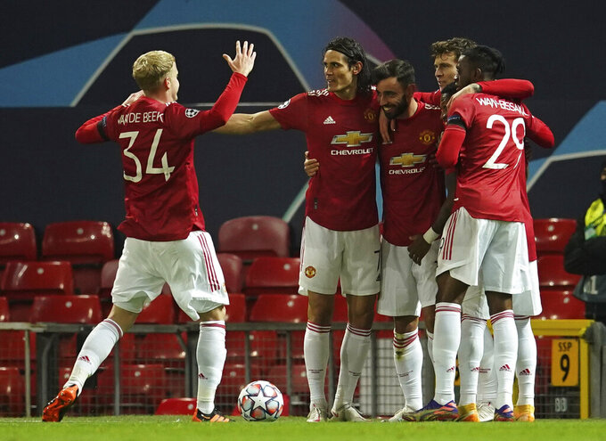 Manchester United's Bruno Fernandes celebrates with team mates scoring the opening goal during the Champions League Group H soccer match between Manchester United and Istanbul Basaksehir at Old Trafford in Manchester, England, Tuesday, Nov. 24, 2020. (AP Photo/Dave Thompson)
