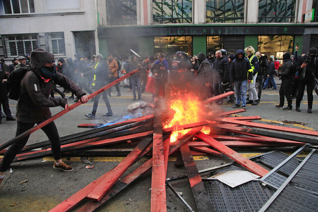 A demonstrators set up a barricade and light fire during a protest against pension reform plans in Paris, Saturday, Dec. 28, 2019. Thousands of protesters opposed to the French government's plan to revamp the retirement system marched through Paris on Saturday, the 14th day of crippling strikes. (AP Photo/Michel Euler)