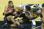 Missouri's Javon Pickett, left, fights for the ball against Wichita State's Clarance Jackson, center, while teammate, Drew Buggs, right, gets in on the action during the second half of an NCAA college basketball game Sunday, Dec. 6, 2020, in Wichita, Kan. (Travis Heying/The Wichita Eagle via AP)