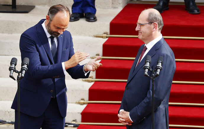 Outgoing French Prime Minister Edouard Philippe, left, applauds newly named Prime Minister Jean Castex, after the handover ceremony in Paris, Friday, July 3, 2020. French President Emmanuel Macron on Friday named Jean Castex, who coordinated France's virus reopening strategy, as the country's new prime minister as the country focuses on reviving an economy hard-hit by the pandemic and months of strict lockdown. (Thomas Samson, Pool via AP)