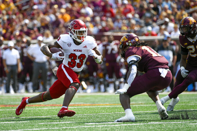 Miami-Ohio running back Kenny Tracy (33) runs past Minnesota defensive back Michael Dixon for a 12-yard gain and a first down in the second half of an NCAA college football game on Saturday, Sept. 11, 2021, in Minneapolis. Minnesota won 31-26. (AP Photo/Craig Lassig)
