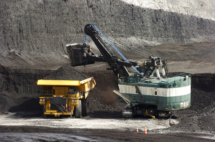 FILE - In this April 4, 2013, file photo, a mechanized shovel loads a haul truck that can carry up to 250 tons of coal at the Spring Creek coal mine near Decker, Mont. The Trump administration says the resumption of coal sales from public lands will result in a negligible increase in greenhouse gas emissions, but critics say that ignores the federal coal programs broader impacts. (AP Photo/Matthew Brown, File)