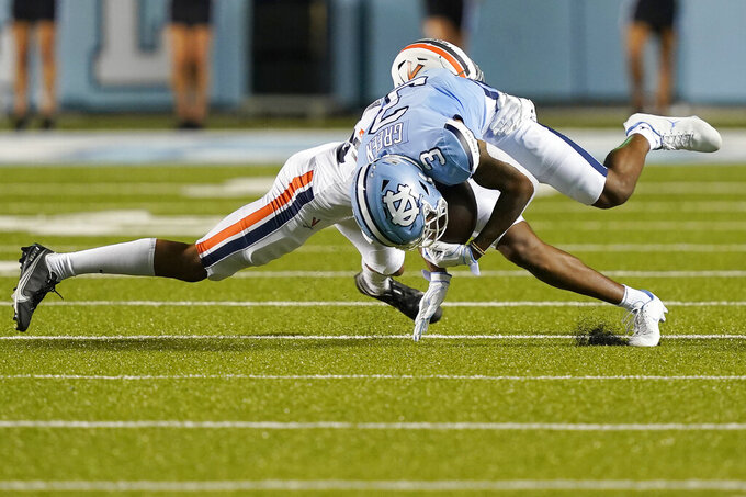 North Carolina wide receiver Antoine Green (3) is tripped by Virginia defensive back Fentrell Cypress II during the first half of an NCAA college football game in Chapel Hill, N.C., Saturday, Sept. 18, 2021. (AP Photo/Gerry Broome)