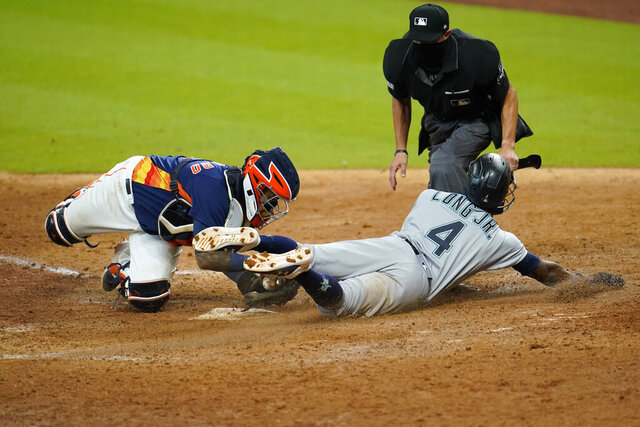 Seattle Mariners' Shed Long Jr. (4) scores as Houston Astros catcher Martin Maldonado reaches to tag him during the eighth inning of a baseball game Sunday, July 26, 2020, in Houston. (AP Photo/David J. Phillip)