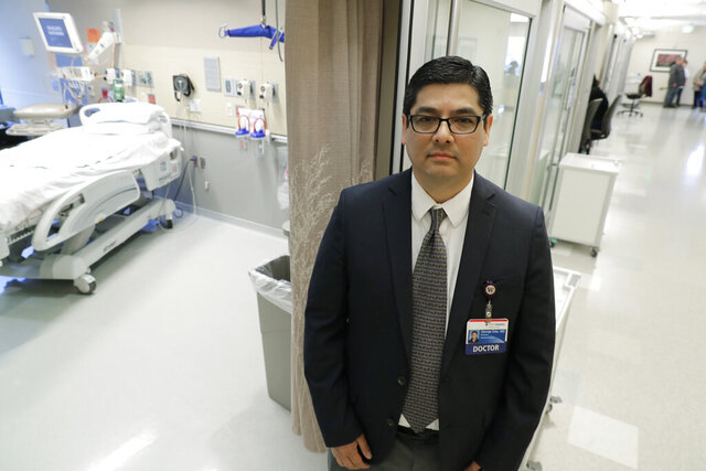 In this photo taken Jan. 23, 2020, Dr. George Diaz, section chief for infectious diseases at Providence Regional Medical Center, poses for a photo in Everett, Wash. Diaz was part of the team that treated the first U.S. patient infected with the new virus from China, who was admitted to the facility on Jan. 20, 2020. The hospital released a statement Monday, Feb. 3, 2020, from the unidentified 35-year-old man that said he has left the hospital and is now in isolation at home, and will be monitored by officials with the Snohomish Health District in coordination with the hospital. (AP Photo/Ted S. Warren)