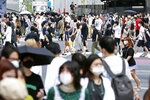 People cross the streets in Tokyo Sunday, Aug. 2, 2020. Confirmed coronavirus cases are hovering at near record levels in Japan, raising worries the pandemic may be growing more difficult to control. The Tokyo government reported more than 290 new cases Sunday, about half in their 20s. (Kyodo News via AP)