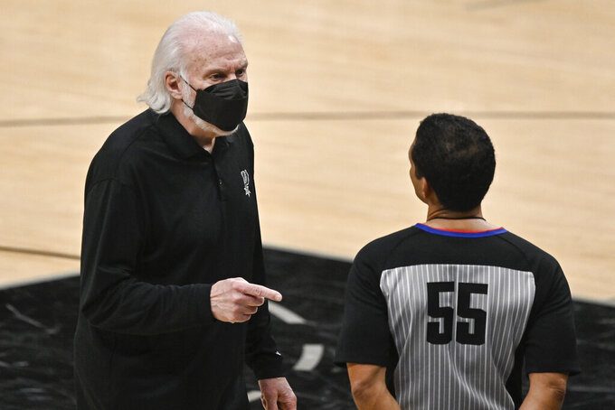 San Antonio Spurs head coach Gregg Popovich, left, talks to referee Bill Kennedy during the second half of an NBA basketball game against the Golden State Warriors, Monday, Feb. 8, 2021, in San Antonio. (AP Photo/Darren Abate)